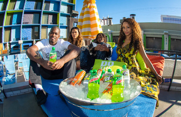 Group of friends sitting next to bucket of Mountain Dew soda.