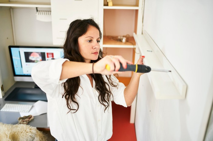 Person using screwdriver to install a wall shelf.