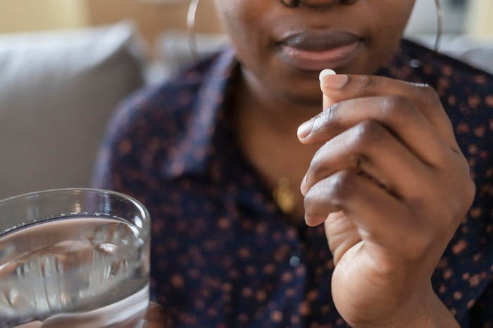 A person holding a glass of water and a pill.