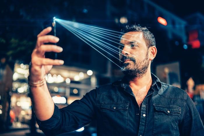 Un homme utilise la reconnaissance faciale sur son téléphone dans une rue.