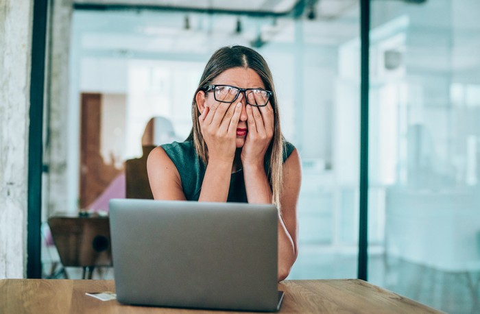 A woman rubs her eyes while sitting in front of a laptop.
