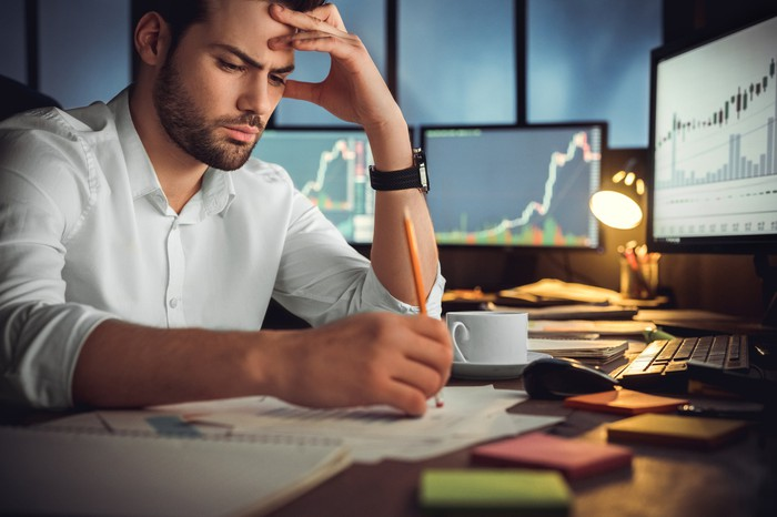Une personne assise à un bureau regarde un graphique boursier et réfléchit.