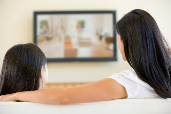 Two people watching a big-screen TV on the couch.