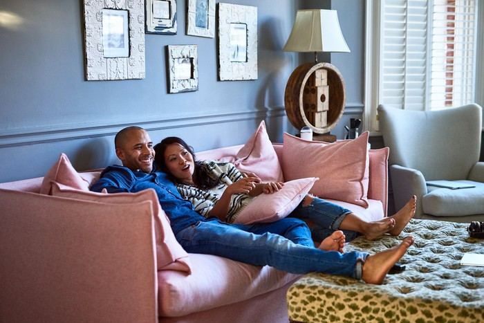 Two people lounge on a bright pink couch in a living room.