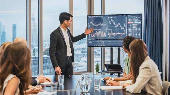 Business person makes a presentation about the stock market in a conference room.