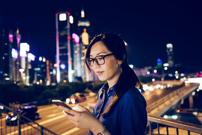Someone using a smartphone. A city skyline is in the background.