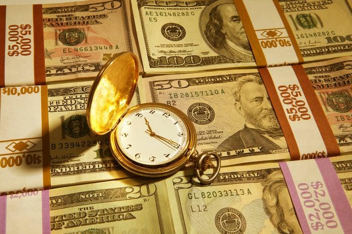 Une montre de poche sur une pile d'argent.