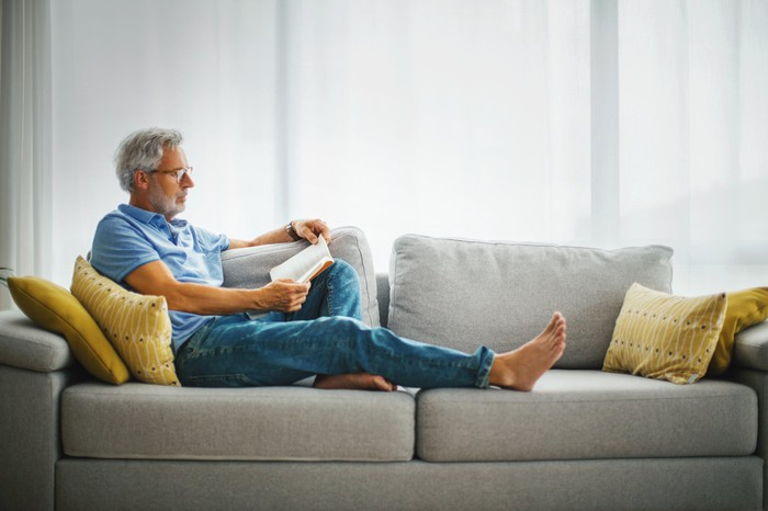 Person reading book on couch