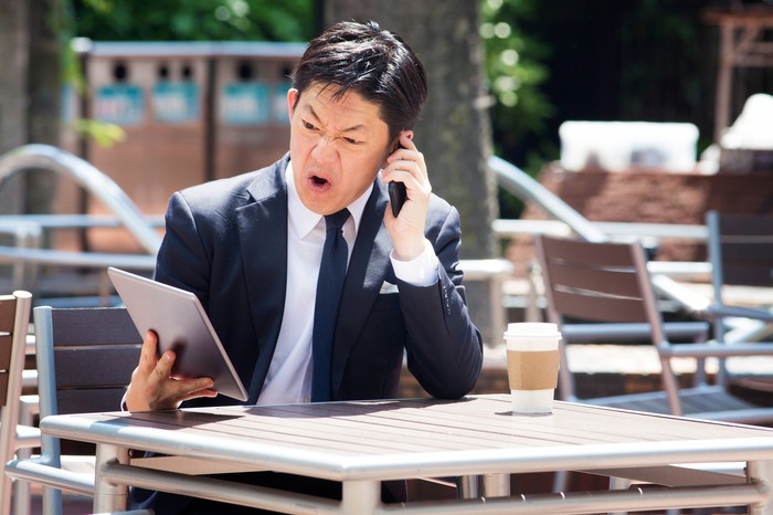A person sitting at an outdoor table with coffee, looking at a tablet in disgust while talking on the phone