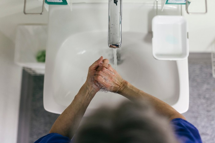 Mature adult washes their hands in a bright white sink basin.