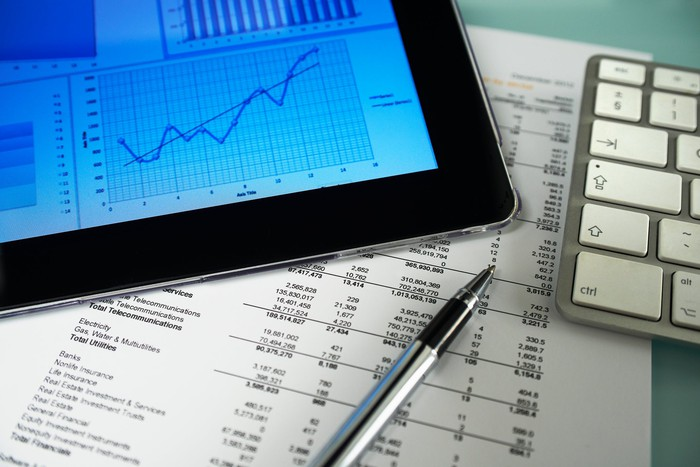 Stock chart on table computer next to paper financial statements.
