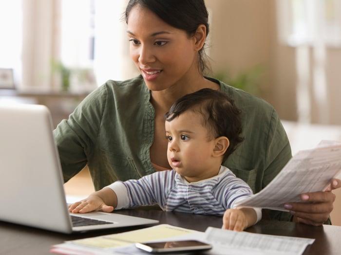 Une personne assise avec un bébé regarde un écran d'ordinateur portable.