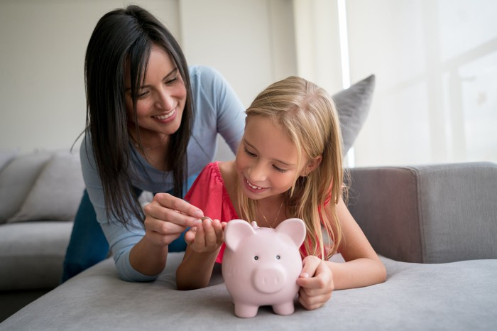 An adult giving a child spare change to put in her piggy bank.