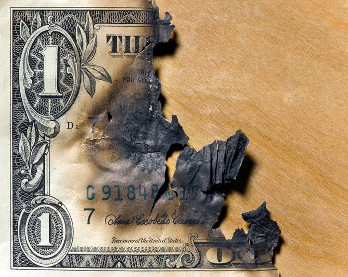 A dollar bill charred and burned down to only a portion left.