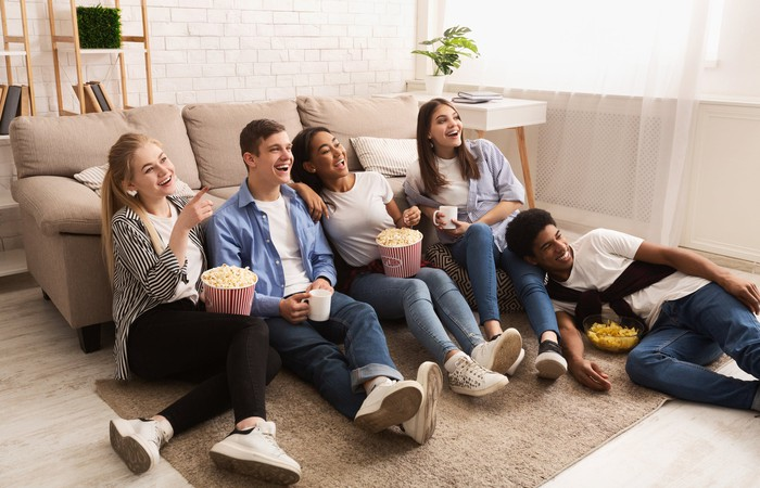 Group of young adults smiling and laughing while watching television and eating popcorn.
