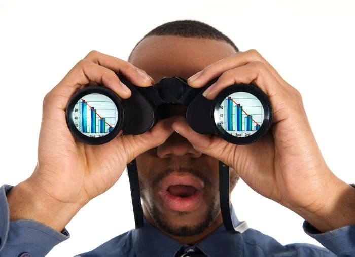 A person looks through binoculars that show declining bar charts in both lenses.