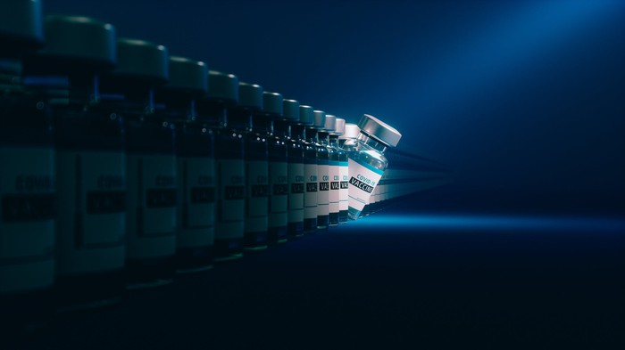 A line of vaccine vials labeled COVID-19 Vaccine, with one tipping over and a light shining on it.