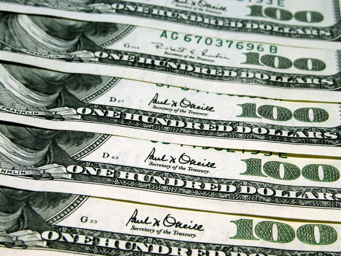 Cinq billets de cent dollars parfaitement échelonnés les uns sur les autres.