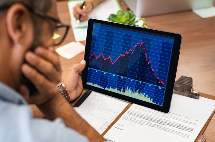 A person intently looking at a plunging stock chart on a tablet.