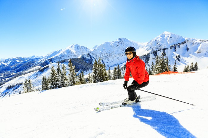 A person skiing down a hill against a mountainous backdrop
