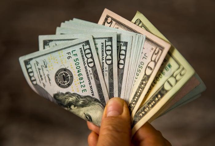 Hand holding assorted U.S. cash.