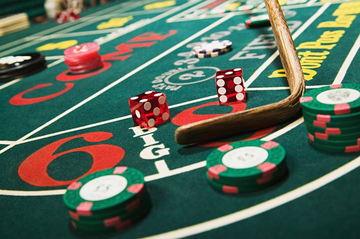 Red dice and casino chips on a craps table.