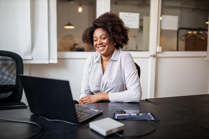 Homme d'affaires assis au bureau et souriant à l'écran d'un ordinateur portable.