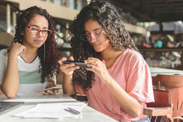 Two women scanning a bill into a digital bank app.