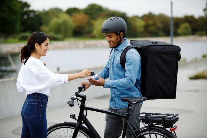 Customer paying delivery person on bike.