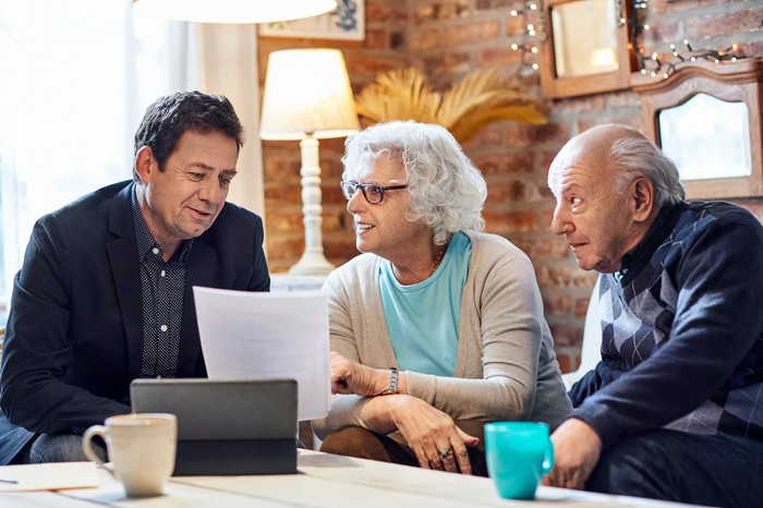 An older couple talks to a man in a suit jacket while all three sit at a coffee table and look at documents.