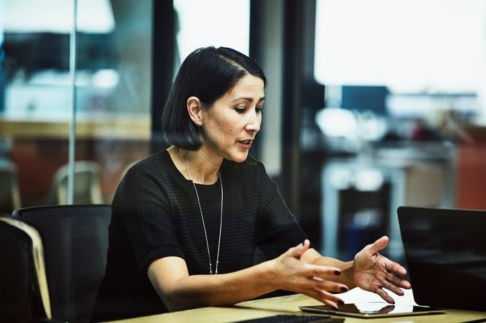 A business woman, perhaps an advisor, explaining data to a colleague or client.