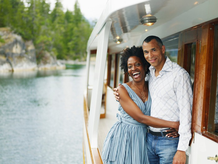 A couple is embracing on a yacht.