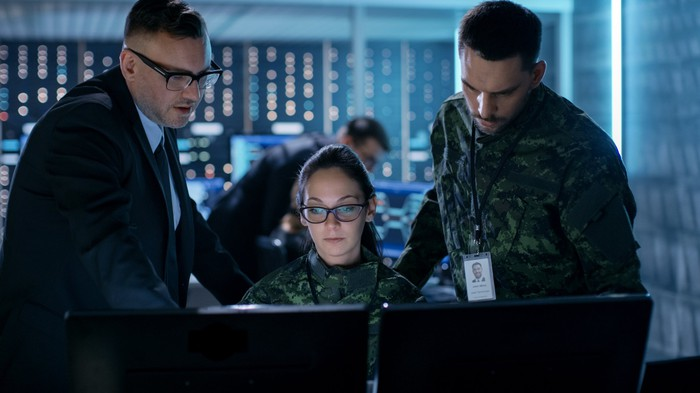 Two soldiers work with an IT professional.