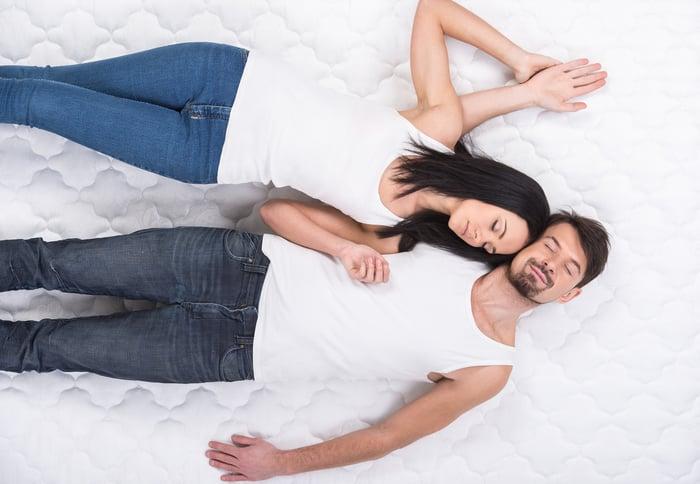 Couple lying on a mattress.