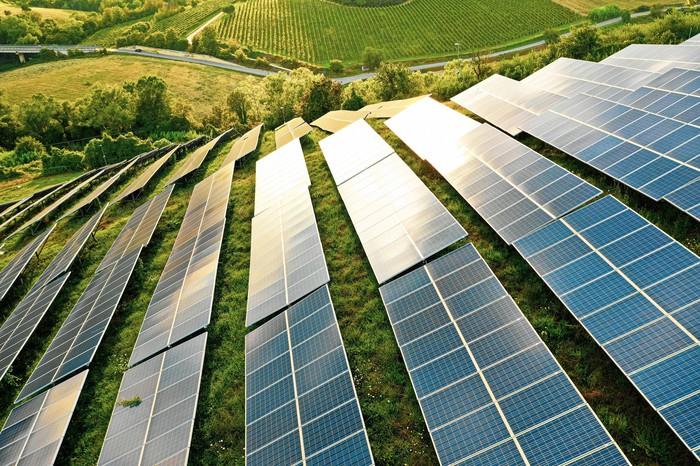 Large solar farm on a large grassy hill.