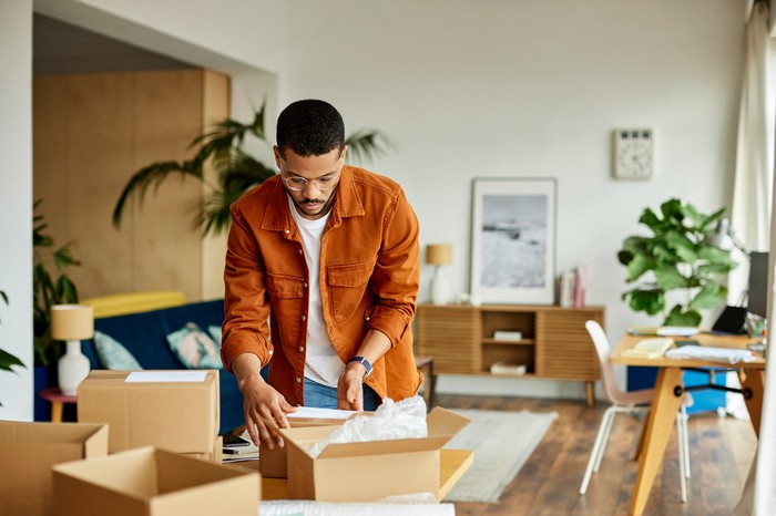 A person looking at boxes in a living room.