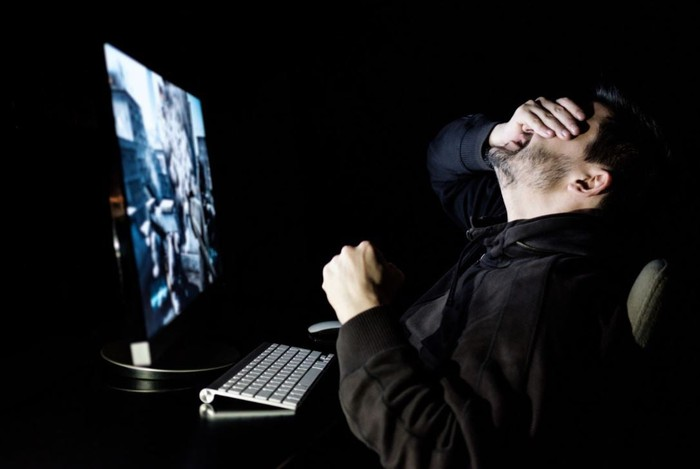 A person in front of a computer holding their head in their hands.