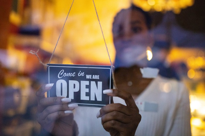 A coffee shop owner hangs a sign that reads come in we are open.