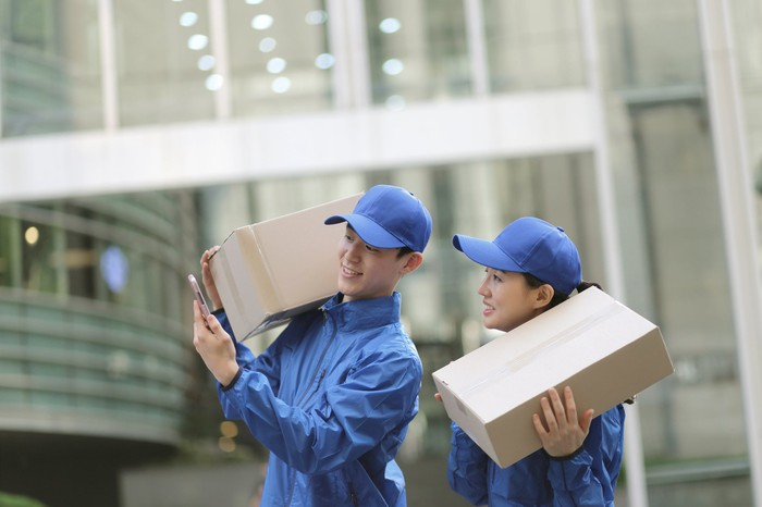 Two delivery people holding cardboard boxes check a smartphone.