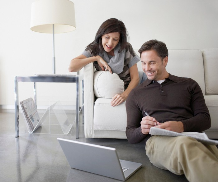 One person lounging on a couch and one person sitting on the floor look at a laptop screen together.