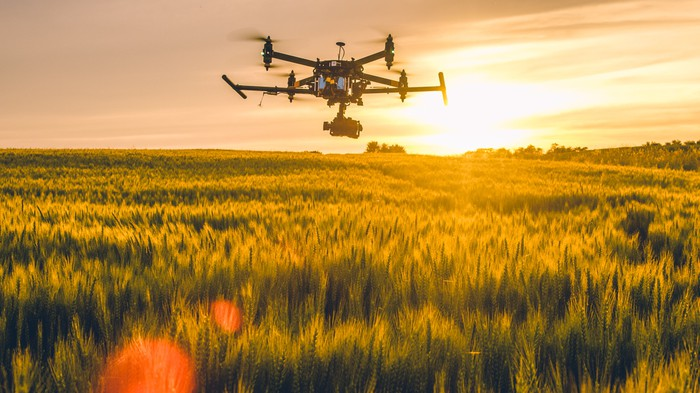A drone flies over a field.