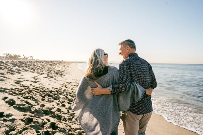 Deux personnes âgées marchant sur la plage.