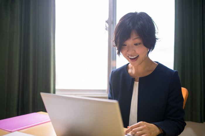 A person sits on a bed looking happily at a laptop screen.