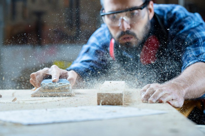 A carpenter is blowing sawdust off a wooden table.