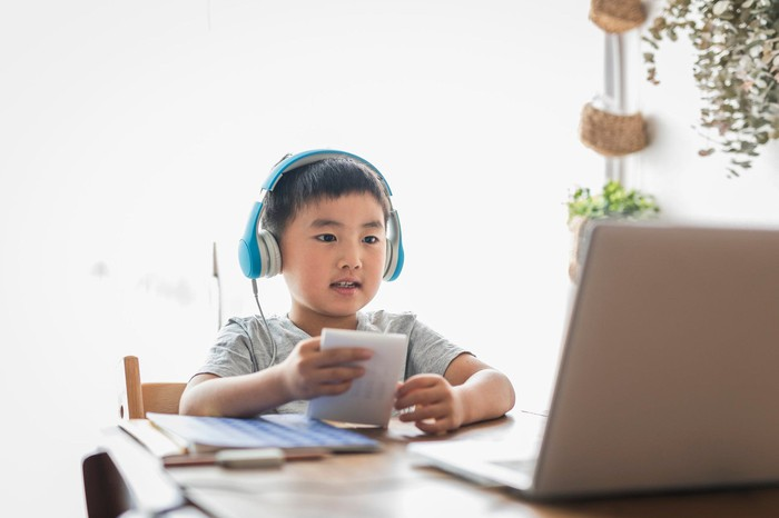 A young child wearing headphones and using a laptop to do schoolwork.