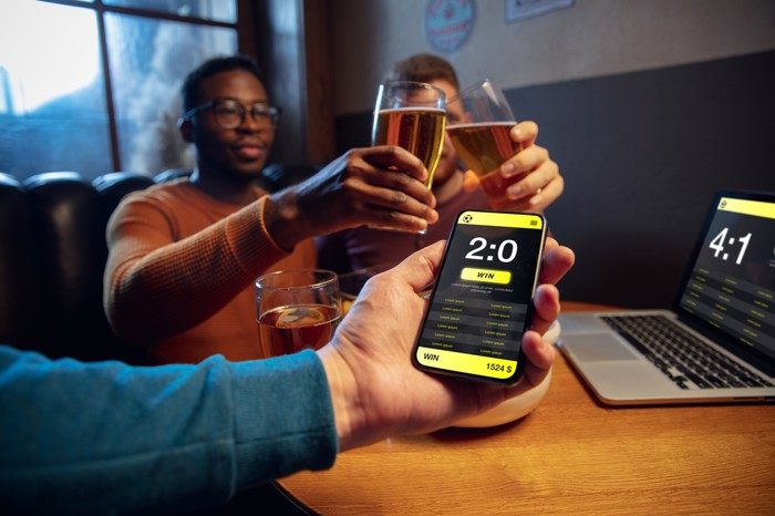 Three friends drinking beer and betting online using a cellphone