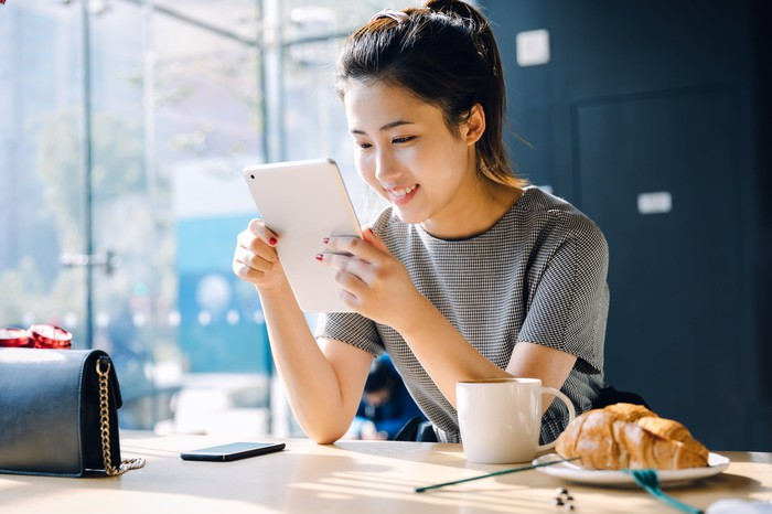 A person reads a tablet while eating breakfast.