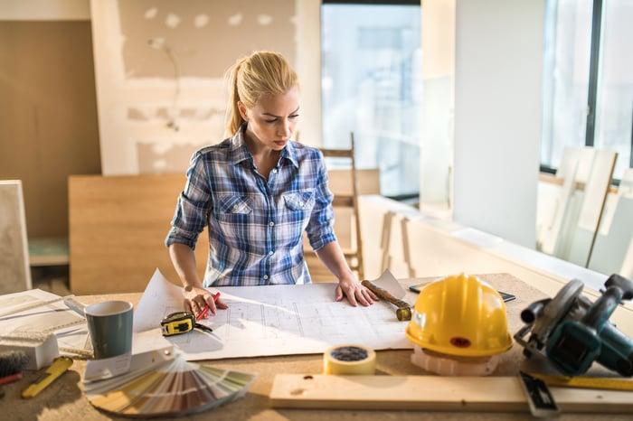 A handyman carpenter consults construction plans.