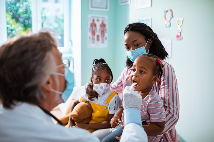 A family with two children at a physician's clinic.