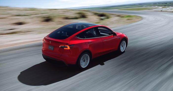 red Tesla Model Y on open road.